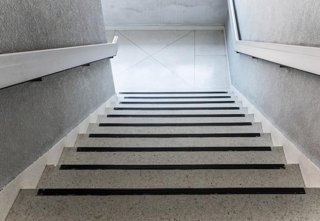 Weißes konkretes treppenhaus mit der metallschiene.