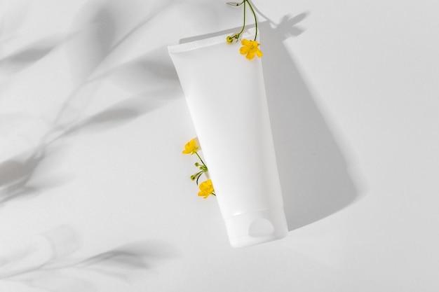 Weißes kosmetisches modell auf weißem hintergrund. konzept des minimalismus in kosmetikverpackungen. weiße kosmetiktube für gesichtscreme. schönheitskonzept-modell.