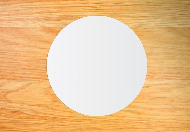 Weißes kreispapier auf vintage braunem holzbrett
