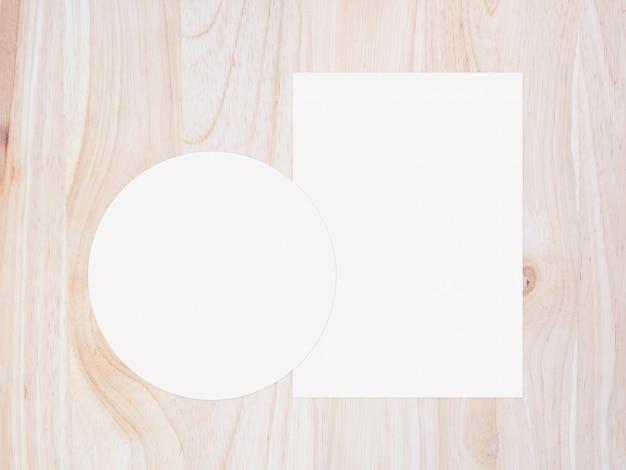 Weißes kreispapier und leeres weißes papier auf vintage braunem holzhintergrund. draufsicht