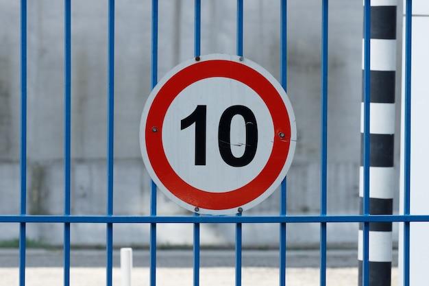 Weißes kreisverkehrsschild mit rotem rand und nummer zehn. geschwindigkeitsbegrenzung 10 km/h. foto in hoher qualität