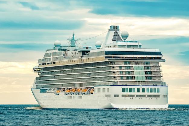 Weißes kreuzfahrtschiff, das sich am bewölkten tag zum meer bewegt