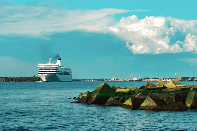 Weißes kreuzfahrtschiff in der stadt riga. tourreisen und wellnessangebote