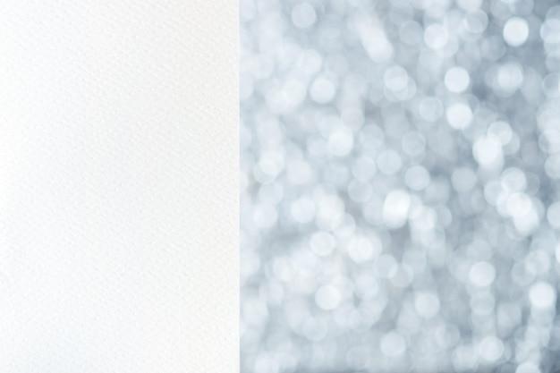 Weißes leeres aquarellpapier am silbernen unschärfe bokeh hellen hintergrund