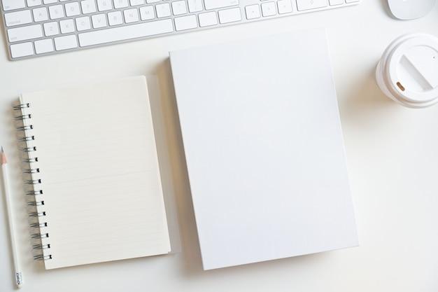 Weißes leeres buch hardcover und notebook mockup auf weißem hintergrund mit tastatur draufsicht