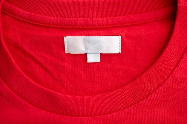 Weißes leeres kleidungsetikett auf neuem rotem baumwollhemdgewebebeschaffenheitshintergrund