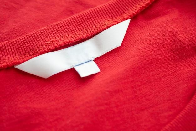 Weißes leeres kleidungsetikett auf neuem roten baumwollhemd-stoffbeschaffenheitshintergrund