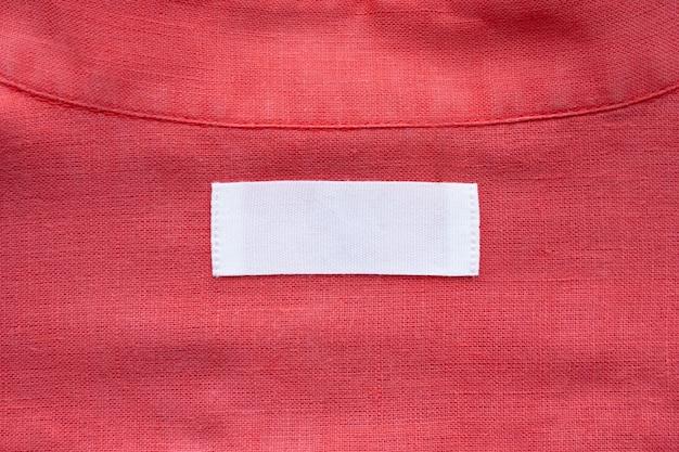 Weißes leeres kleidungsetikett auf rotem leinenhemd-stoffbeschaffenheitshintergrund