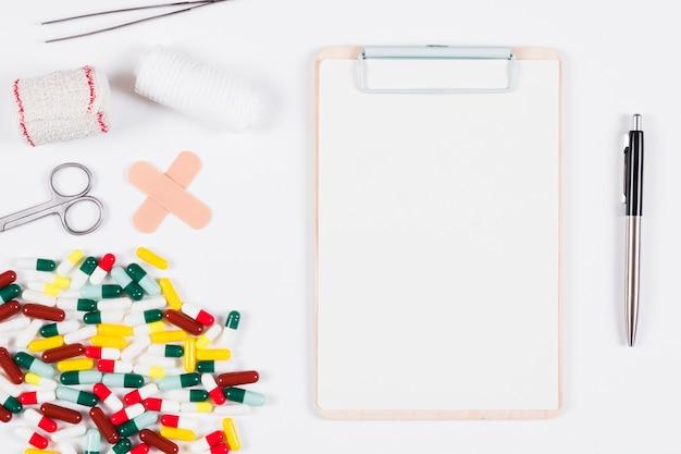 Weißes leeres klemmbrett mit stift und medizinische bedarfe und ausrüstungen auf weißem hintergrund