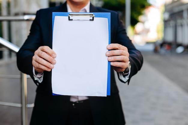 Weißes leeres leeres modell der nahaufnahme des papierblattes in den männlichen händen - kopieren sie raum