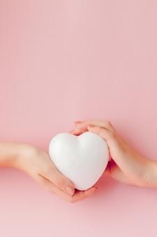 Weißes leeres liebesherz in den händen auf rosa hintergrund.