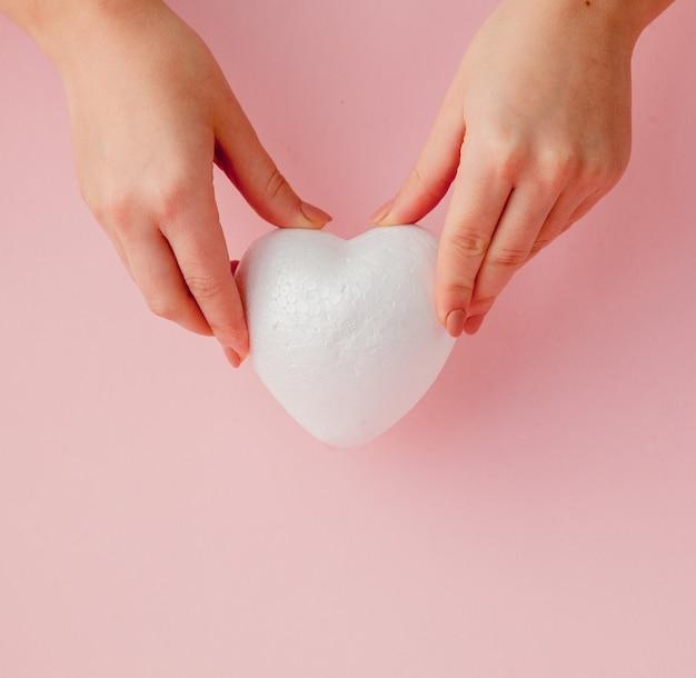 Weißes leeres liebesherz in den händen auf rosa tisch