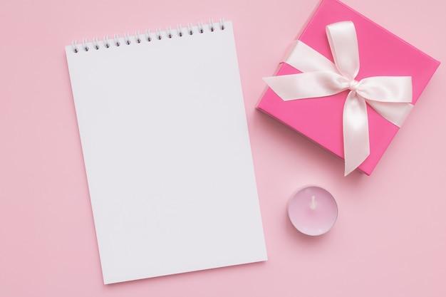 Weißes leeres notizblockblatt, rosa kerze, geschenkbox auf rosa hintergrund