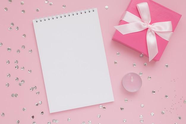 Weißes leeres notizblockblatt, rosa kerze, geschenkbox und konfetti auf rosa wand, glücklicher valentinstag