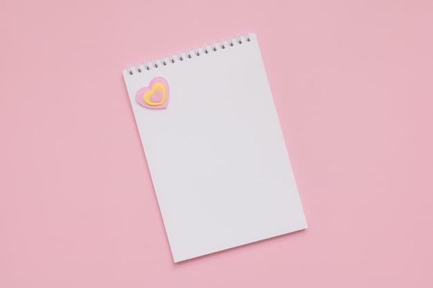 Weißes leeres notizblockblatt, rosa und gelbes herz auf einer rosa wand, glücklicher valentinstag