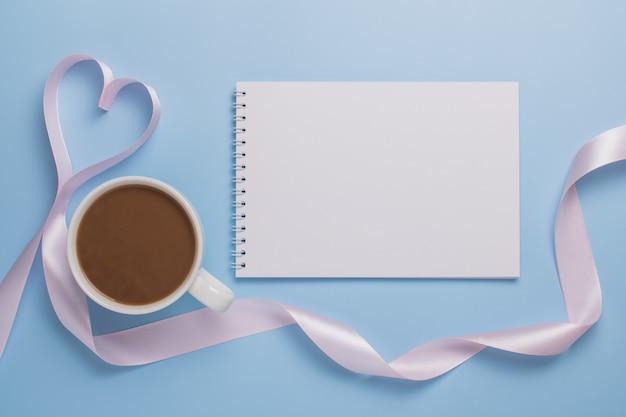 Weißes leeres notizblockblatt, tasse kaffee und rosa band in der form eines herzens auf einem blauen hintergrund. valentinstag konzept.