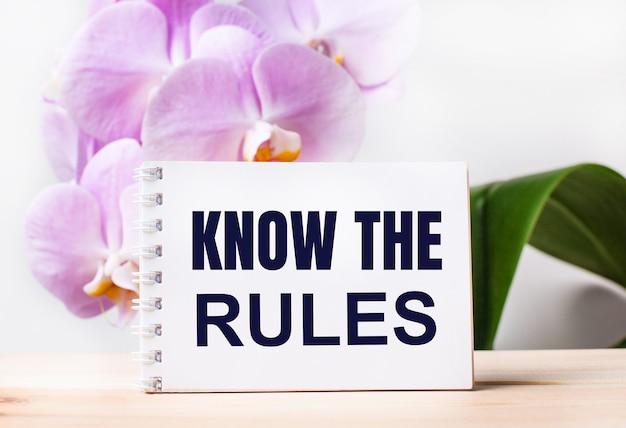 Weißes leeres notizbuch mit dem text know the rules auf dem tisch vor dem hintergrund einer hellrosa orchidee.