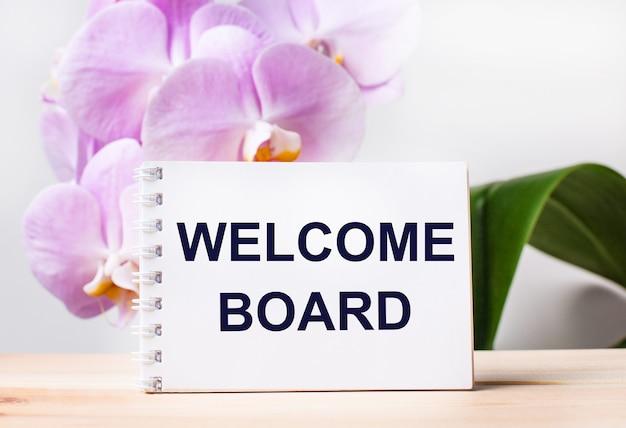 Weißes leeres notizbuch mit dem text welcome board auf dem tisch vor dem hintergrund einer hellrosa orchidee.