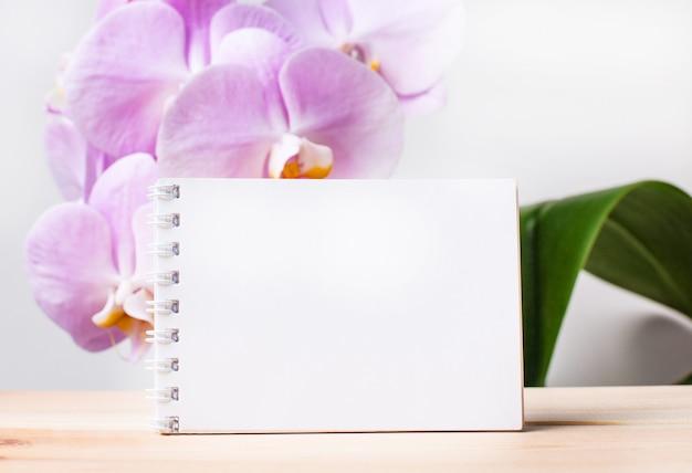 Weißes leeres notizbuch mit platz zum einfügen von text auf dem tisch gegen die oberfläche einer hellrosa orchidee