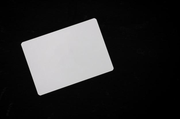 Weißes leeres papier auf einem schwarzen hölzernen schreibtisch