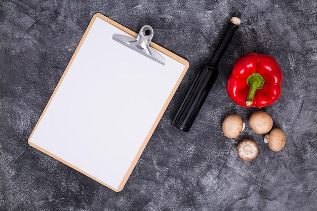 Weißes leeres papier in zwischenablage mit paprika; pilz und flasche auf schwarzem strukturiertem hintergrund