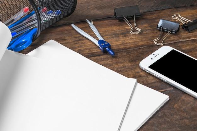 Weißes leeres papier mit schreibwaren und smartphone auf holztisch