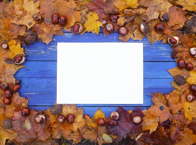 Weißes leeres papierblatt auf den gealterten blauen holzbrettern mit herbstblättern und kastanien.