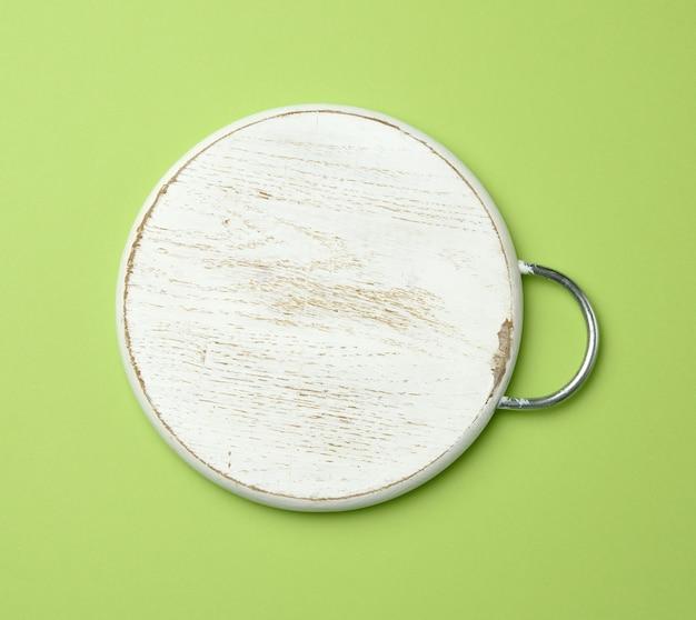 Weißes leeres rundes schneidendes holzbrett, grüner hintergrund, draufsicht