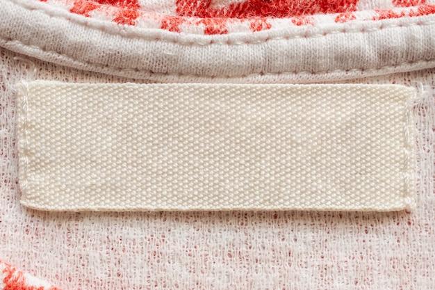 Weißes leeres wäschepflege-kleidungsetikett auf baumwollhemd