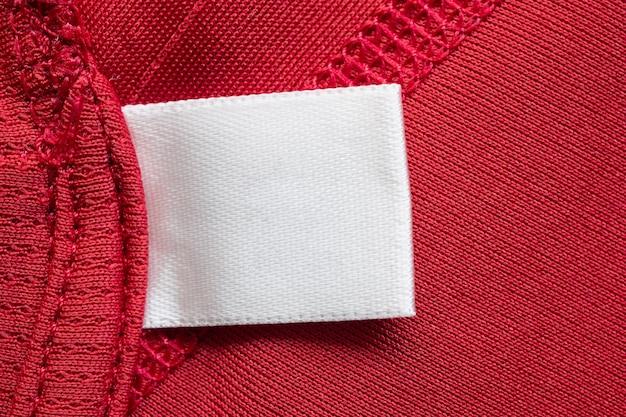 Weißes leeres wäschepflege-kleidungsetikett auf rotem polyester-sporthemdhintergrund