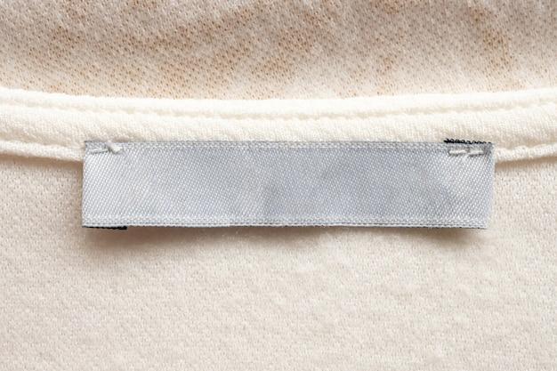 Weißes leeres wäschepflegetuchetikett auf stoffstruktur
