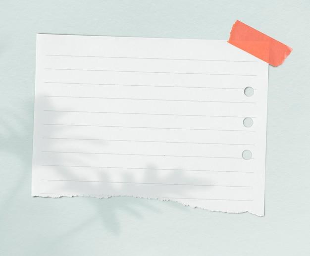 Weißes liniertes musterpapier mit blattschatten an einer wand