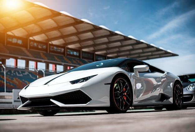 Weißes luxussportlimousinenauto, das auf der rennspur, vorderseiteansicht steht.