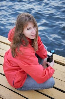 Weißes mädchen der rothaarigen im rosa wassermantel, der auf dem pier des sees sitzt und tee von der thermoskanne trinkt