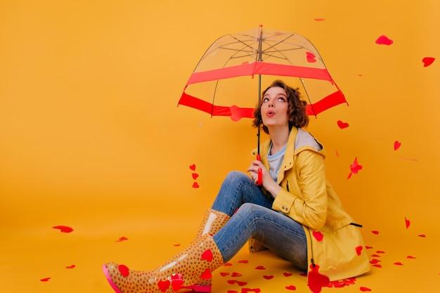 Weißes mädchen mit regenschirm, der unter herzregen aufwirft. studioaufnahme der gewinnenden jungen frau, die fotoshooting am valentinstag genießt.