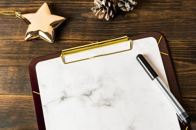 Weißes marmorklemmbrett und schwarzer markierungsstift mit goldenem stern