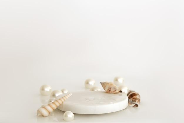 Weißes marmorpodest mit perlen, muscheln und wassertropfen auf weißem hintergrund. podium für produkt, kosmetische präsentation. kreatives mock-up. sockel oder plattform für schönheitsprodukte.
