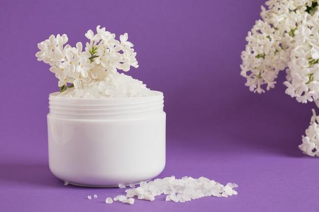 Weißes meersalz im plastikglas und weiße lila blumen auf lila hintergrund natürliches körperpflegekosmetikkonzept