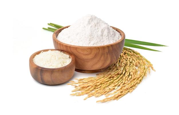 Weißes mehl in holzschale mit weißem reis und reisohren isoliert auf weißer oberfläche