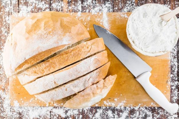 Weißes mehl verbreitete sich über dem brotlaib mit messer auf schneidebrett
