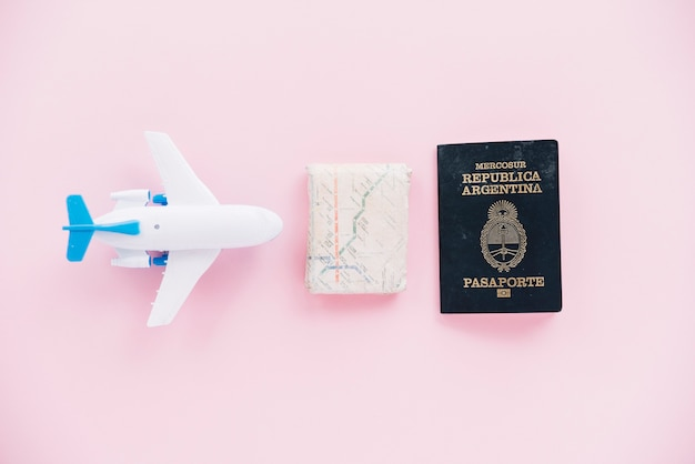 Weißes miniaturflugzeug; karte und pass auf rosa hintergrund