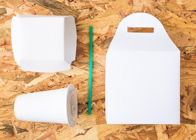 Weißes mitnehmernahrung mit trinkhalm des türkises auf hölzernem hintergrund