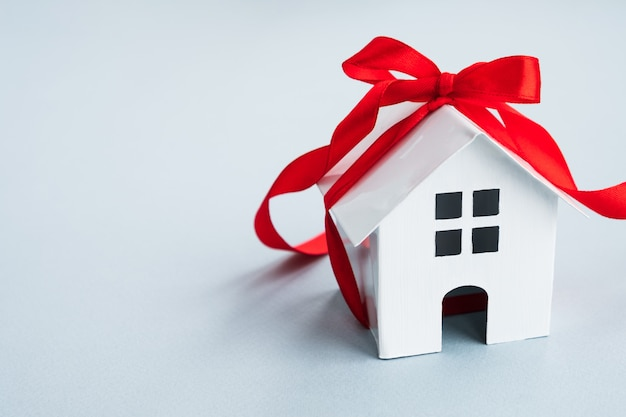 Weißes modellhaus mit rotem band. neues wohnkonzept