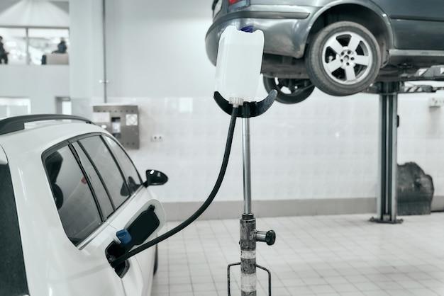 Weißes modernes auto tankt nach geplanter diagnose und überholung mit benzin aus dem weißen kanister in der tankstelle, bevor der glückliche besitzer es wegnimmt. auto-service und techniker-konzept