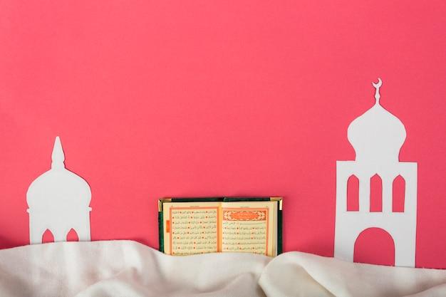 Weißes moscheepapier schnitt mit einem offenen heiligen islamischen kuran über dem roten hintergrund heraus