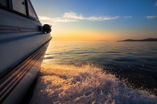 Weißes motorboot, das sich schnell zum sonnenuntergang bewegt