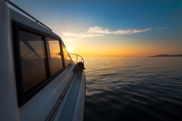 Weißes motorboot fährt zum sonnenuntergang