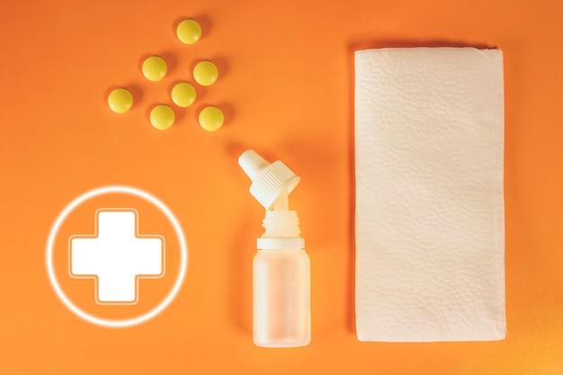 Weißes nasenspray aus kunststoff, tabletten und papiertaschentücher mit dem symbol des medizinischen kreuzes auf orangefarbenem hintergrund - sinusitis, geniantritis, rhinitis und andere erkrankungen der hno-organe.