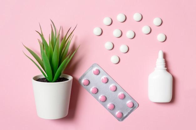 Weißes nasenspray mit tabletten und kräutern auf rosafarbenem hintergrund als kräuterbehandlung von nasenverstopfung