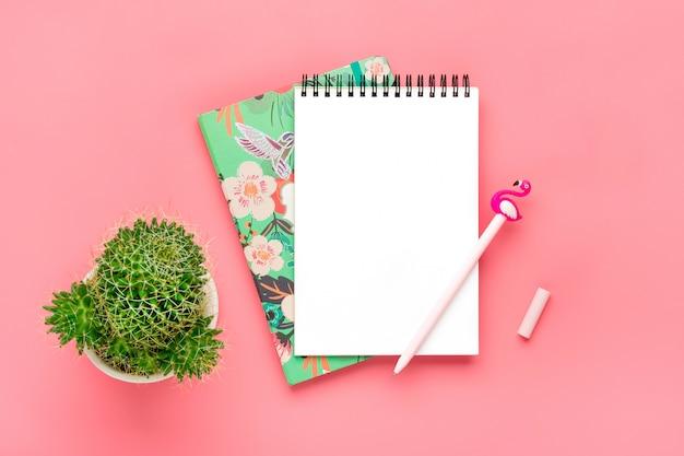 Weißes notizbuch für anmerkungen, kerze, stiftflamingo, hauptblumensucculent, rosa hintergrund
